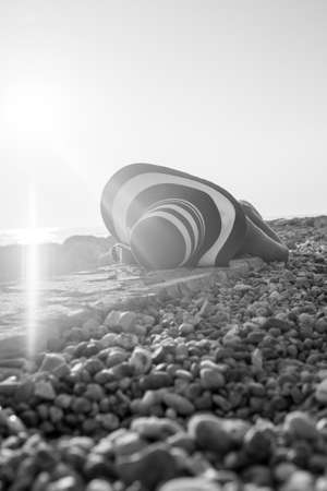 Monochrome image of a woman sunbathing on a stony beach in a low angle view across the pebbles. Stock Photo