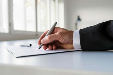 Low view of businessman hand signing business contract on white office desk.