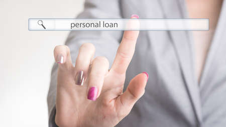 Female hand touching a web search bar with the word personal loan on a virtual screen as she seeks further information. Stock Photo