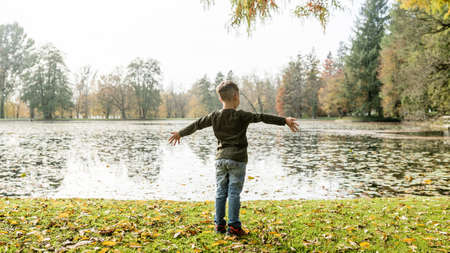 Young kid enjoying the autumn weather standing with outstretched arms on the bank of a lake or river celebrating the peace and tranquility, with lateral copy space.