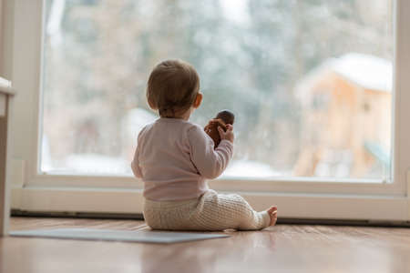 Little baby girl watching the winter snow outdoors as she sits on a wooden floor in front of a large view window clutching a toy in a low angle view.