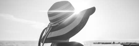 Monochrome image of a woman with sunburst over her stripped straw hat looking into the distance over the ocean.