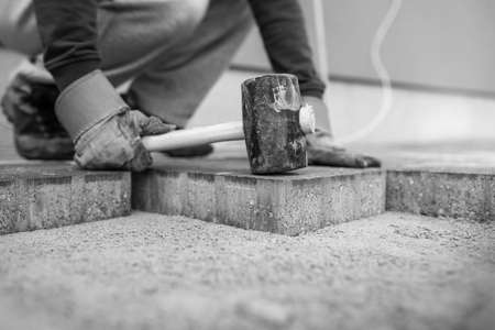 Worker laying new paving bricks or stones placing them in position with a rubber mallet on a foundation in greyscale image.