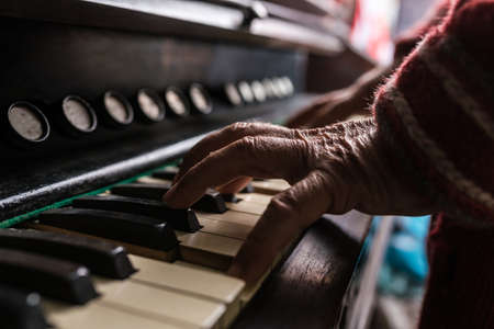 Old man playing the organ in a close up view of his wrinkled hands on the keyboard as he enjoys his music.