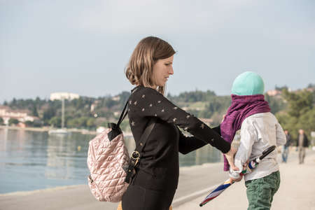 Young mother dressing her son in a pullover as they enjoy a day walking on a waterfront promenade in the sunshine.