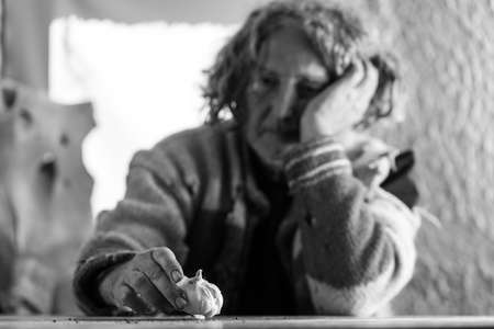 Monochrome image of concerned man with long hair and a sweater full of holes sitting at a table indoors looking sad at a bulb of garlic.