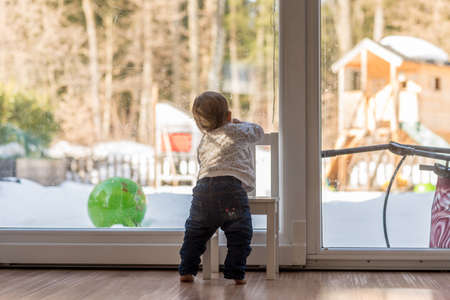 Cute little toddler balancing on a chair staring out of a large view window at home overlooking a winter garden with snow.