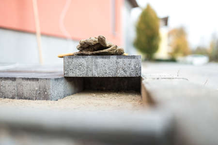 New paving stone resting above newly installed bricks outdoors in an urban environment balancing across a gap that is too tight with work gloves on top.