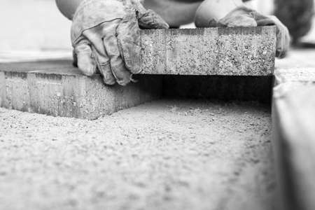 Greyscale image of workman laying a paving brick placing it on the sand foundation. Stockfoto