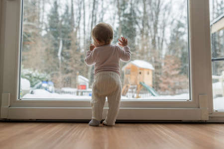 Rear view of baby girl standing in front of dirty window looking outside at a snowy garden. Stock Photo