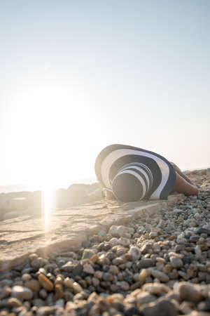 Woman sunbathing on a stony beach basking in the hot summer sun in a low angle view across the pebbles of the top of her sunhat.