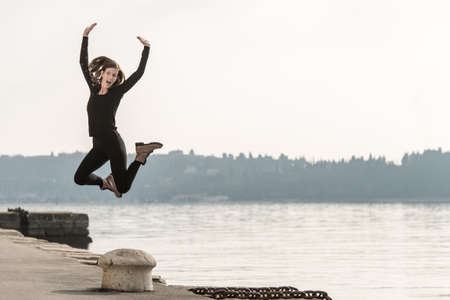 Young woman jumping for joy above a bollard on a quay overlooking a lake or the ocean on a misty atmospheric day.