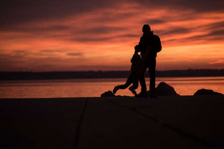 Young boy playing on rocks with his father silhouetted against a glowing orange marine sunset reflected in a calm ocean. Stock Photo