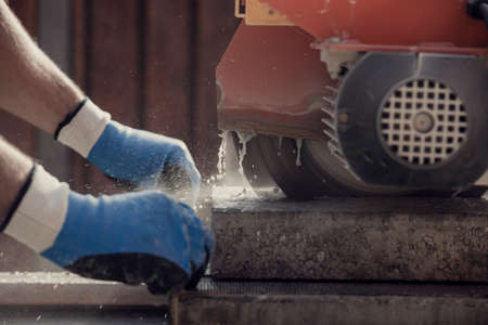 Retro image of workman using an angle grinder or circular saw to cut a concrete block in a close up side view of his hands and the power tool.