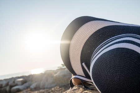 Vrouw in een grote zonnehoed liggend zonnebaden op een kiezelstrand genietend van de hete zomerzon in een close-up uitzicht op de top van de hoed.