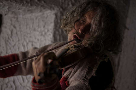 Old man with tousled long hair singing as he plays a violin totally immersed in the music with his eyes closed. Фото со стока