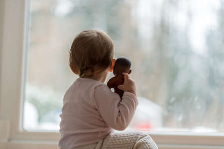 Little baby girl hugging a toy watching the winter snow outdoors as she sits in front of a large view window. Reklamní fotografie