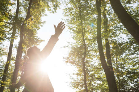 Man standing with his arms spread widely in forest with bright sunlight coming from behind him.