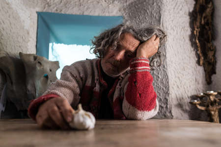 Older man with tousled hair looking at a bulb of fresh garlic as he sits at a rustic table in a cottage resting his head on his hand with thoughtful expression in a low angle view.
