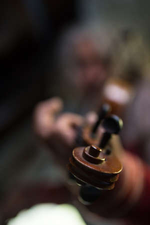 Man playing a violin with focus to scroll and pegs. Shallow dof.