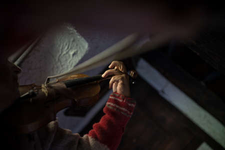 Man in a tattered old torn jersey playing a violin in a darkened room in a beam of light. Banco de Imagens