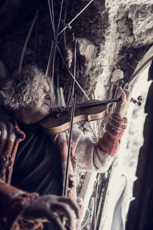 Retro toned image of a man with tousled long hair in old torn sweater full of holes playing music on a classical wooden violin.