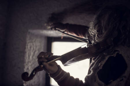 Retro toned artistic image of and older man playing violin enthusiastically indoors next to a window. Stockfoto