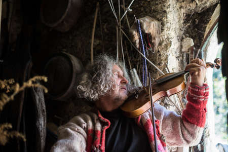 Older bohemian man in torn old sweater playing violin in an old rustic house next to and open door.