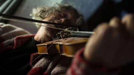 Musician enjoying his music as he plays a violin in a low angle view with focus to the instrument and bow.