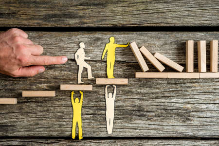 Teamwork and stopping the domino effect concept with paper cutouts of men supporting others on steps while they prevent a line of dominoes from falling.