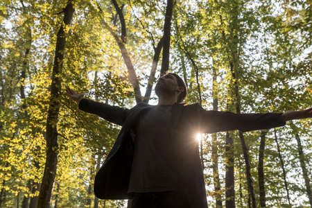 Person spreading out arms in woods with sun behind trees.