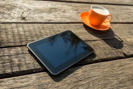 Blank digital tablet and coffee cup on a rustic wooden table.