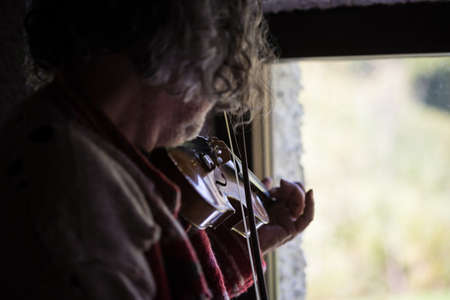 Male musician with tousled long hair playing a classical violin with missing string at home by the window in rear view.