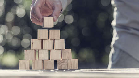 Retro toned image of man building a pyramid with blank wooden blocks outdoors against sparkling bokeh.
