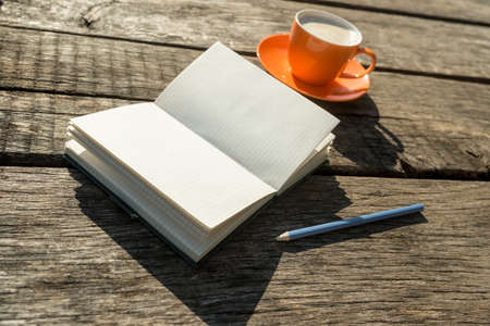 Blank white book with pencil and coffee cup over old weathered wooden table for theme about memories and introspection. Foto de archivo - 102128846