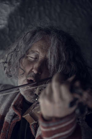 Retro toned image of  man with gray hair and beard singing as he plays a violin with his eyes closed.