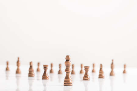 Black king with chess figures on white table in a conceptual image with copy space. Stock Photo