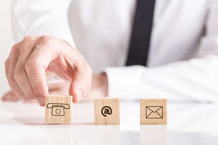 Geschäftsmann, der hölzerne Würfel auf weißen Tisch mit E-Mail- und Telefonpiktogrammen, konzeptionelle Figur der Geschäftskontakte setzt.