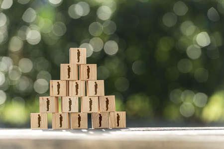 Pyramid of toy wooden blocks with human icons of a businessman conceptual of management structure, human resources, business hierarchy, teamwork and employees on a garden table with copy space. Stok Fotoğraf