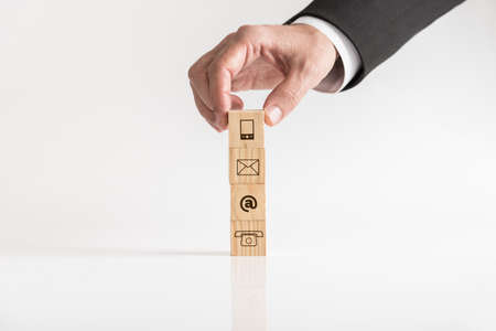 Businessman hand arranging blocks with means of communications icons, viewed in close-up against white background.