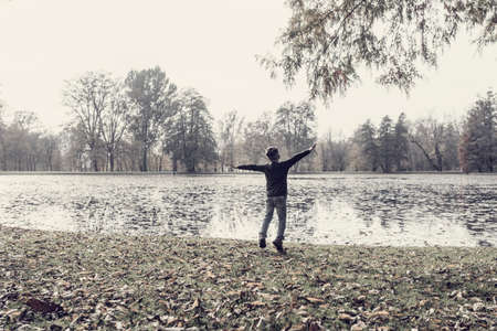 Energetic young boy jumping for joy with outstretched arms with lake and fallen leaves on the grass, toned retro effect.