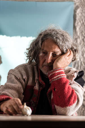Thoughtful older man with tousled long hair and a jersey full of holes sitting at a wooden table indoors looking at a fresh bulb of garlic on the table in a low angle view. Stock Photo