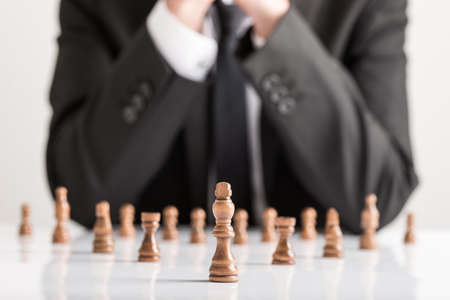 Businessman in business suit planning strategy with dark chess figures on white table.