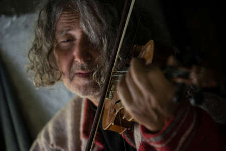 Elderly man immersed in his music as he plays a violin in a close up cropped view of his face. 스톡 콘텐츠