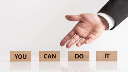 You can do it business concept with copy space. Businessman hand showing wooden blocks with inscription, viewed in close-up against light background.