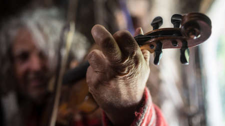 Close up of the hand of an elderly man playing music on a classical wooden violin indoors with focus to his hand.