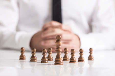 Businessman with clasped hands planning strategy with dark chess figures on white table. Reklamní fotografie