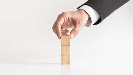 Businessman hand placing small wooden blocks on top of each other, viewed in close-up on glossy surface and against white background. Stock Photo