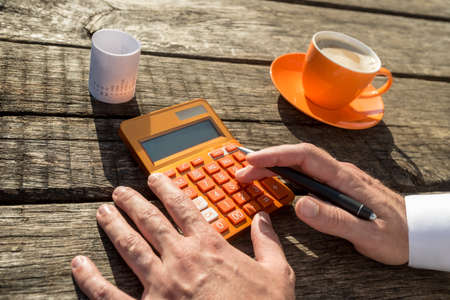 Businessman using a colorful orange manual calculator next to coffee cup and receipt.