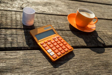 Colorful orange manual calculator next to coffee cup and receipt on old cracked wooden table.
